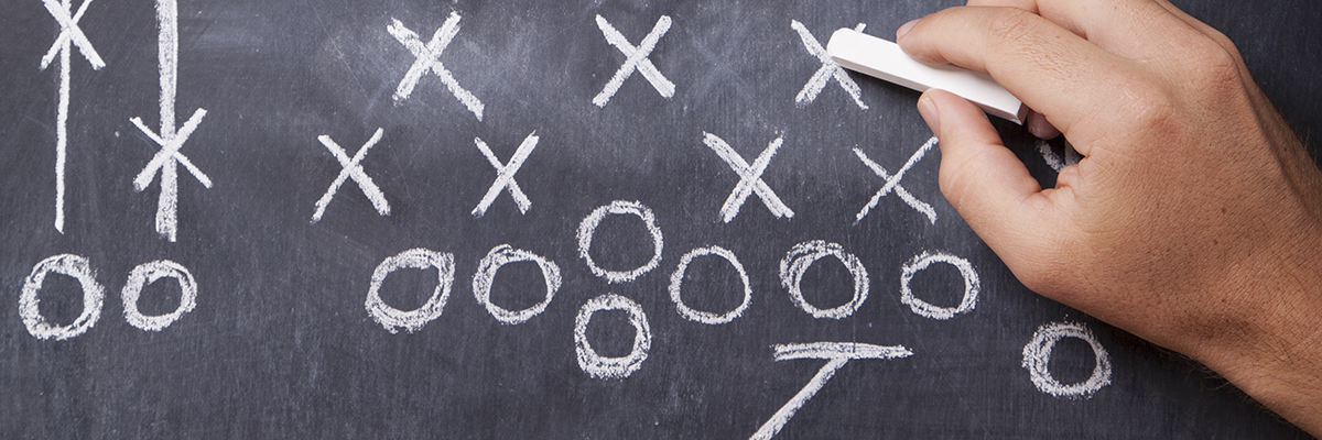A hand draws a football play on a chalkboard with chalk leaving room for copy.